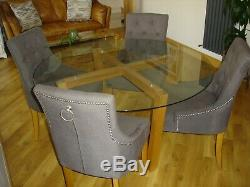Next glass, oak dining table and four grey knocker chairs. (COULD DELIVER)